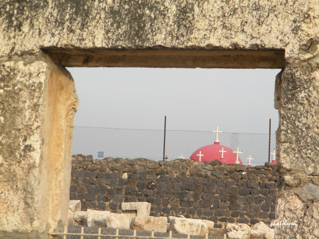 pink domed greek orthodox church seen from a synagouge ruins in capernaum