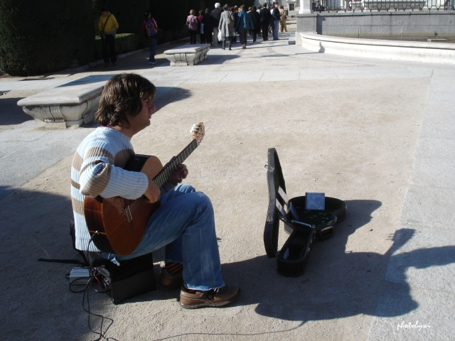 a solo musician in front of the royal palace in madrid