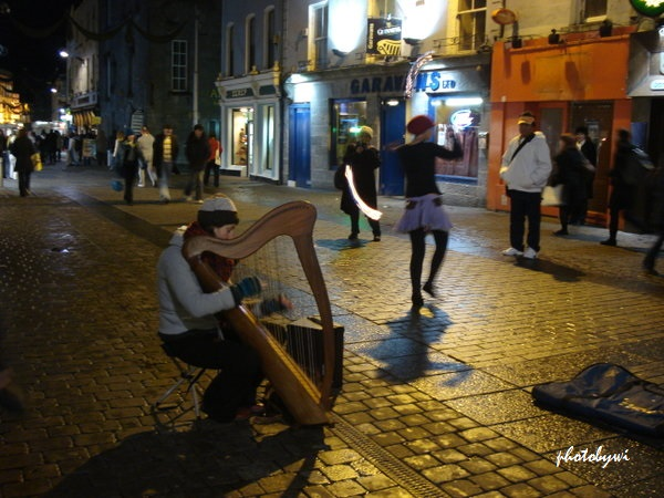 a harpist playing for a fire dancer taken in galway city, ireland