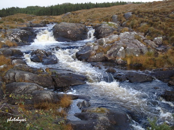 a short three-step waterfalls bisecting a rocky field captured from a bus ride to connemara, ireland